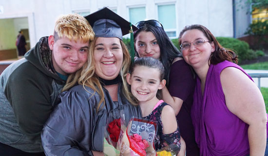 Female graduate with children and flowers