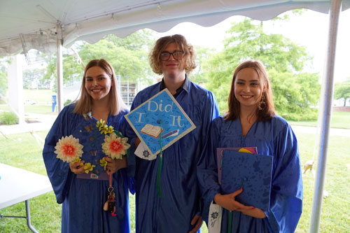 three students posing with their cap at the Ocean Achievement center graduation